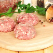 Raw meatballs with spices on wooden table — Stock Photo