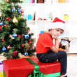Foto de Stock  : Little boy with big gift and clock in anticipation of New Year