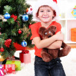 Royalty-Free Stock Photo: Little boy in Santa hat sits near Christmas tree with gift in hands
