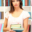 Young attractive female student holding her school books in library — Stock Photo #17213479