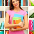 Young attractive female student holding her school books in library — Stock Photo #17213481