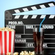 Movie clapperboard, cola and popcorn on blue background — Stockfoto