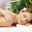 Beautiful woman in spa salon getting massage, on palm leaves background — Stock Photo