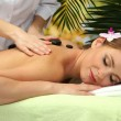 Beautiful woman in spa salon getting massage with stones, on palm leaves background — Stock Photo #17213973