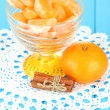 Tasty mandarine's slices in glass bowl on blue background — Stock Photo