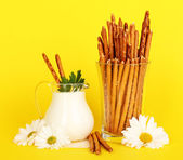 Tasty crispy sticks in glass cup on yellow background — Stock Photo
