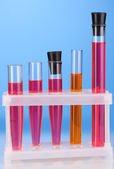 Test-tubes with a colorful solution on blue background close-up — Photo