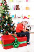 Liten pojke med stora gåva och klocka i väntan på nya året — Stockfoto