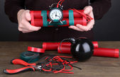 Human makes timebomb on wooden table on black background — Stock Photo