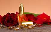Women's perfume in beautiful bottle with rose on brown background — Stock Photo