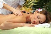 Beautiful woman in spa salon getting massage with stones, on palm leaves background — Stock Photo