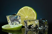 Ice cubes with lime on darck blue background — Stock Photo