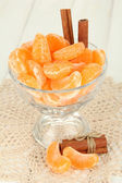 Tasty mandarine's slices in glass bowl on light background — Stock Photo