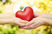 Red heart in woman and man hands, on green background — Photo