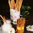 Tasty crispy sticks with pitcher and glass with sour cream on wooden table close-up — Stock Photo #17384591