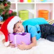 Royalty-Free Stock Photo: Little boy  fell asleep with gift in his hands under the Christmas Tree waiting for Santa Claus to come
