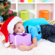 Little boy fell asleep with gift in his hands under the Christmas Tree waiting for Santa Claus to come — Stock Photo #17384965
