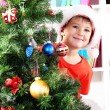 Royalty-Free Stock Photo: Little boy in Santa hat peeks out from behind Christmas tree
