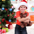 Little boy in Santa hat sits near Christmas tree with gift in hands — Stock Photo #17384989