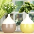 Decorative flowers in vases on windowsill — Stock Photo