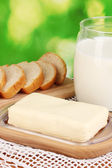 Butter on wooden holder surrounded by bread and milk on natural background close-up — Stock Photo
