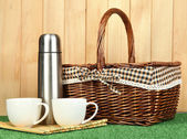 Metal thermos with cups and basket on grass on wooden background — Stock Photo