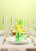 Table setting in green and yellow tones on color background — Stock Photo