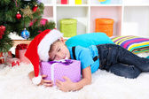 Little boy fell asleep with gift in his hands under the Christmas Tree waiting for Santa Claus to come — Stock Photo