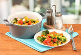 Vegetable stew in gray pot on wooden table on bright background — Stock Photo