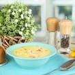 Fragrant soup in blue plate on table on window background close-up — Stock Photo