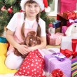 Little girl in Santa hat near the Christmas tree in festively decorated room - Stock Photo