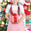 Happy little girl with Christmas toys in festively decorated room - Stock Photo