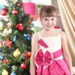 Beautiful little girl in holiday dress in festively decorated room - Stock Photo