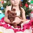 Beautiful little girl in holiday dress with toy in hands in festively decorated room - Stock Photo