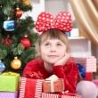 Dreaming little girl in red dress surrounded by gifts in festively decorated room - Stock Photo