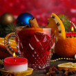 Fragrant mulled wine in glass with spices and oranges around on wooden table on red background - Stock Photo