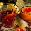 Fragrant mulled wine in glass with spices and oranges around on wooden table - 