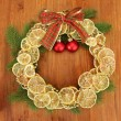 Christmas wreath of dried lemons with fir tree and balls, on wooden background - Foto de Stock
