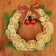 Christmas wreath of dried lemons with fir tree and balls, on wooden background - Foto Stock
