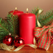 Two candles and christmas decorations, on brown background - Stock Photo