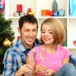 Young happy couple holding glasses with champagne near Christmas tree at home — Stock Photo #17400345