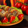 Tasty grilled meat and vegetables on plate, on fire background — Stock Photo #17400395