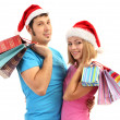 Young couple in Santa hats shopping and holding many shopping bags isolated on white — Stock Photo