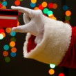 Stock Photo: SantClaus hand holding credit card, on garland background