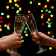 Woman hand with glasses of champagne, on garland background - Stock fotografie