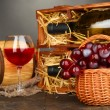 Wooden case with wine bottles, barrel, wineglass and grape on wooden table on grey background - Zdjęcie stockowe