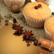 Tasty muffin cakes with spices on burlap and cup of coffee, on brown background — Stock Photo
