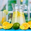 Citrus lemonade in pitcher and glass of citrus around on blue wooden table on window background — Stock Photo