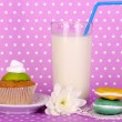 Glass of fresh new milk with confectionery on purple polka dot background — Stock Photo