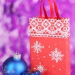 Christmas paper bag for gifts on purple background — Photo